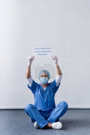 Photo for Middle aged doctor in medical mask and cap holding placard with i stay at work for you, you stay at home for us lettering while sitting on white - Royalty Free Image