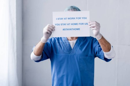 Photo for Mature doctor covering face with placard with i stay at work for you, you stay at home for us lettering on white - Royalty Free Image