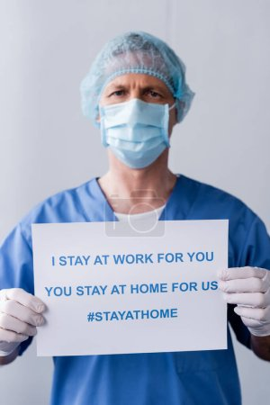Photo for Mature doctor in medical mask and cap holding placard with i stay at work for you, you stay at home for us lettering on grey - Royalty Free Image