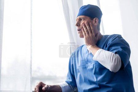 Photo pour Médecin fatigué et d'âge moyen dans le chapeau de gommage debout près de la fenêtre à l'hôpital et toucher le visage - image libre de droit