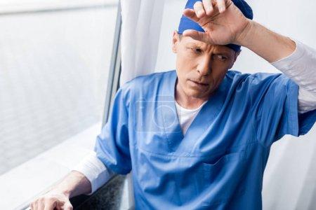 Photo pour Médecin fatigué et d'âge moyen dans le chapeau de gommage touchant le front près de la fenêtre à l'hôpital - image libre de droit