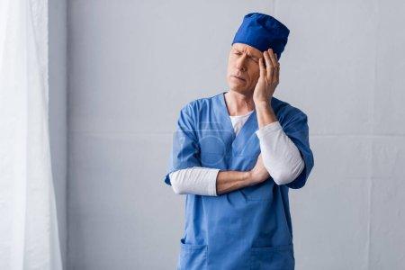 Photo pour Docteur fatigué et d'âge moyen en chapeau bleu gommage touchant la tête sur gris - image libre de droit