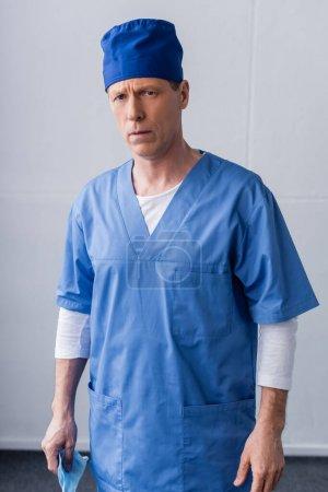 Photo pour Mature médecin en bleu gommage chapeau tenant masque médical sur gris - image libre de droit