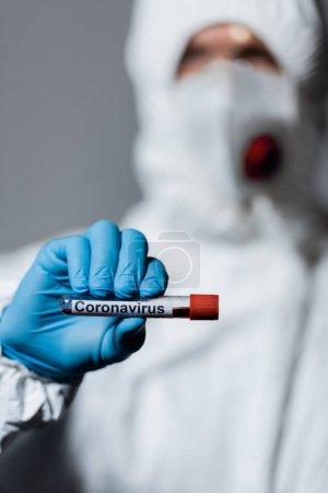 Photo pour Foyer sélectif du médecin mature en combinaison hazmat, masque médical et lunettes tenant le tube à essai avec lettrage coronavirus isolé sur gris - image libre de droit