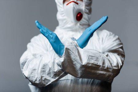 Photo pour Vue recadrée du médecin mature en combinaison hazmat, masque médical et gants en latex debout avec les bras croisés isolés sur gris - image libre de droit