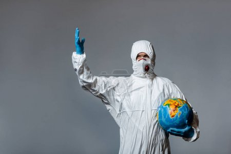mature doctor in hazmat suit, medical mask and latex gloves holding globe and gesturing isolated on grey