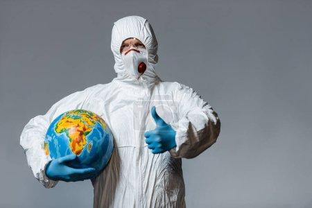 Foto de Hombre con traje de materiales peligrosos y máscara médica sosteniendo globo y mostrando el pulgar hacia arriba aislado en gris - Imagen libre de derechos