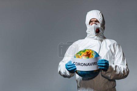 Foto de Hombre con traje de materiales peligrosos y máscara médica sosteniendo globo y papel con letras de coronavirus aisladas en gris - Imagen libre de derechos