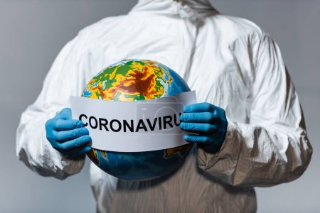 cropped view of man in hazmat suit holding globe and paper with coronavirus lettering isolated on grey