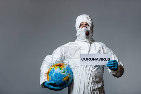 man in personal protective equipment holding globe and paper with coronavirus lettering isolated on grey