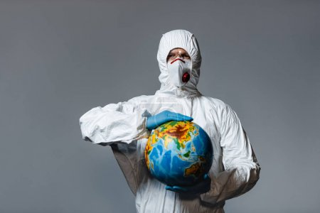 man in personal protective equipment holding globe isolated on grey