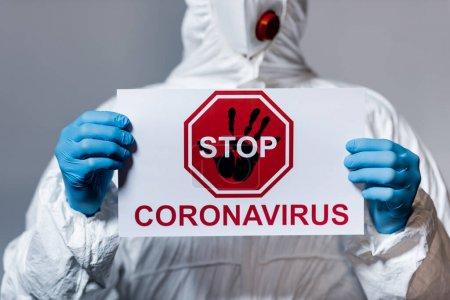 Photo pour Vue recadrée du médecin adulte en combinaison Hazmat tenant une pancarte avec lettrage stop coronavirus isolé sur gris - image libre de droit