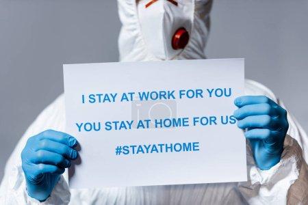 Photo pour Vue recadrée du médecin mature en combinaison Hazmat tenant la pancarte avec je reste au travail pour vous, vous restez à la maison pour nous lettrage isolé sur gris - image libre de droit