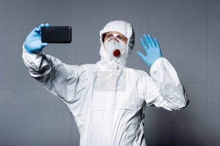 Photo pour Homme en équipement de protection individuelle prenant selfie et agitant la main sur gris - image libre de droit