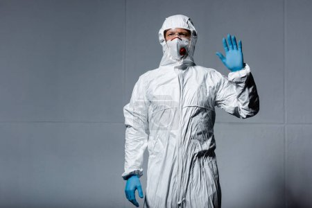 Photo for Man in personal protective equipment waving hand on grey - Royalty Free Image