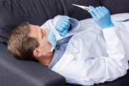 Photo pour Médecin mature en masque médical et gants en latex regardant le thermomètre numérique tout en étant couché et en toussant sur le canapé - image libre de droit