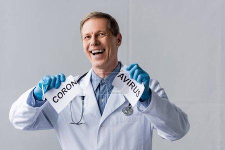 Photo pour Médecin gai et mature en gants de latex tenant du papier déchiré avec lettrage coronavirus sur gris - image libre de droit