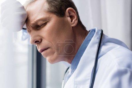 zmęczony lekarz w średnim wieku z zamkniętymi oczami w pobliżu okna w klinice