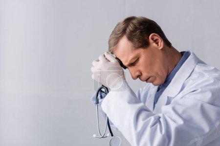 Photo pour Docteur fatigué et mature avec les yeux fermés tenant stéthoscope sur gris - image libre de droit
