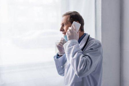 Photo pour Médecin heureux et mature en manteau blanc parlant sur smartphone près de la fenêtre - image libre de droit