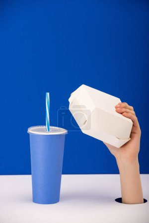 cropped view of woman holding carton box near paper cup with soft drink isolated on blue