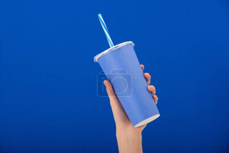 cropped view of woman holding paper cup with soft drink isolated on blue