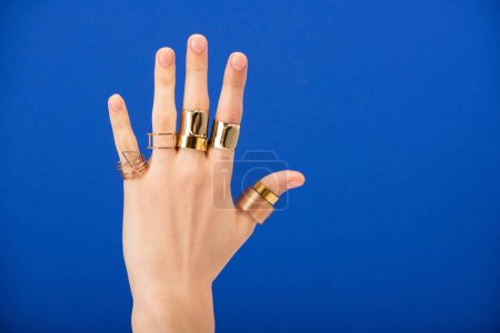Photo pour Cropped view of woman with rings on hand isolée on blue - image libre de droit