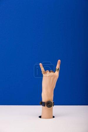 Photo pour Vue recadrée de la femme avec montre-bracelet à portée de main montrant signe de roche isolé sur bleu - image libre de droit