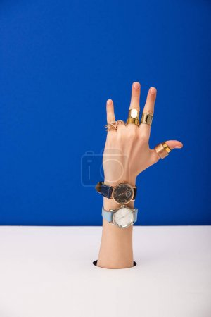 Photo for Cropped view of woman with wristwatches on hand and golden rings isolated on blue - Royalty Free Image