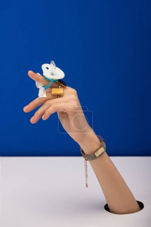 Photo for Cropped view of woman with bracelet and rings holding silicone pacifier isolated on blue - Royalty Free Image