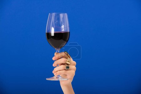 Photo for Cropped view of woman with rings on fingers holding glass with red wine on blue - Royalty Free Image