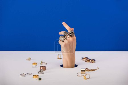 Photo pour Cropped view of woman with bracelet on hand near rings isolated on blue - image libre de droit