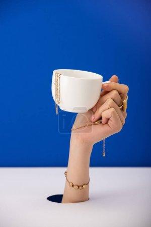 Photo pour Crocheté vue de femme avec bracelet à la main tasse avec chaîne dorée isolée sur bleu - image libre de droit