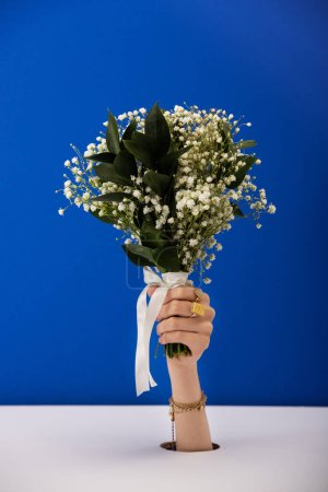 Photo pour Crocheté vue de femme avec bracelet et anneaux tenant bouquet de fleurs de printemps isolé sur bleu - image libre de droit