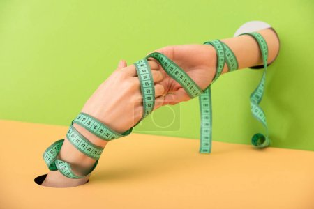Photo for Cropped view of woman with measuring tape and clenched hands on green and orange - Royalty Free Image