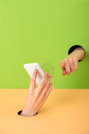 Photo for Cropped view of woman pointing with finger and holding smartphone on green and orange - Royalty Free Image