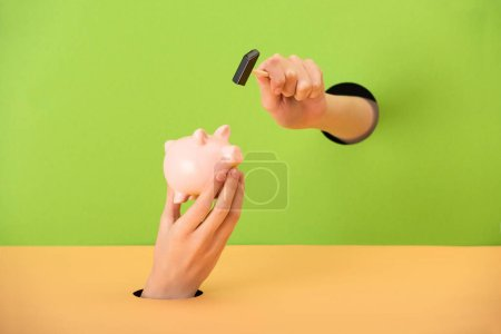 cropped view of woman holding small hammer near pink piggy bank on green and orange