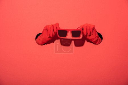 Photo for Cropped view of woman in gloves holding stylish sunglasses on red - Royalty Free Image