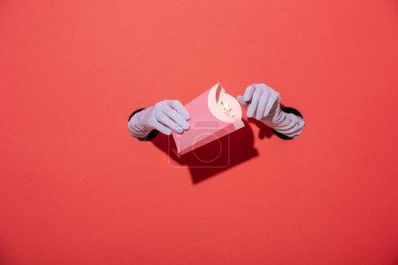 Photo pour Vue recadrée de la femme dans des gants tenant seau de maïs soufflé sur rouge - image libre de droit