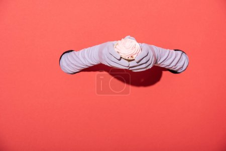 Photo for Cropped view of woman in gloves holding sweet dessert on red - Royalty Free Image