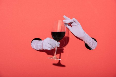 Photo for Cropped view of woman in gloves holding glass with red wine on red - Royalty Free Image