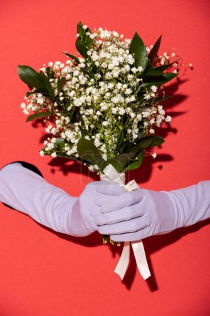 Photo for Cropped view of woman in gloves holding bouquet of white spring flowers on red - Royalty Free Image