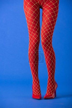 Photo pour Vue recadrée de la femme en collants résille et talons rouges debout sur bleu - image libre de droit