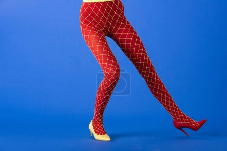 Photo for Cropped view of trendy model in fishnet tights, yellow and red heels posing on blue - Royalty Free Image
