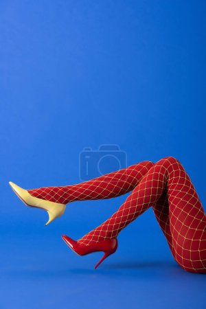 Photo for Cropped view of woman in fishnet tights, yellow and red heels lying on blue - Royalty Free Image