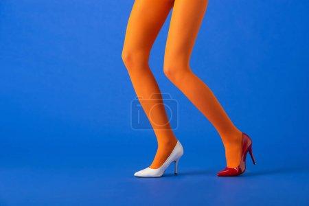 Photo pour Vue recadrée du modèle élégant en collants orange, talons blancs et rouges posant sur bleu - image libre de droit