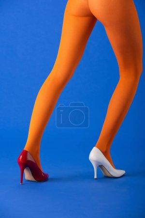 Photo pour Vue recadrée du modèle à la mode en collants orange, talons blancs et rouges posant sur bleu - image libre de droit