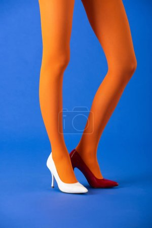 Photo pour Vue recadrée du modèle tendance en collants lumineux, talons blancs et rouges posant sur bleu - image libre de droit