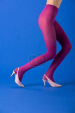 Photo for Cropped view of model in bright purple tights and shoes standing on blue - Royalty Free Image