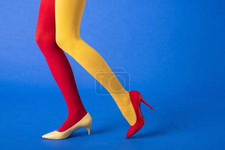 Photo for Cropped view of model in yellow and red tights and shoes posing on blue - Royalty Free Image